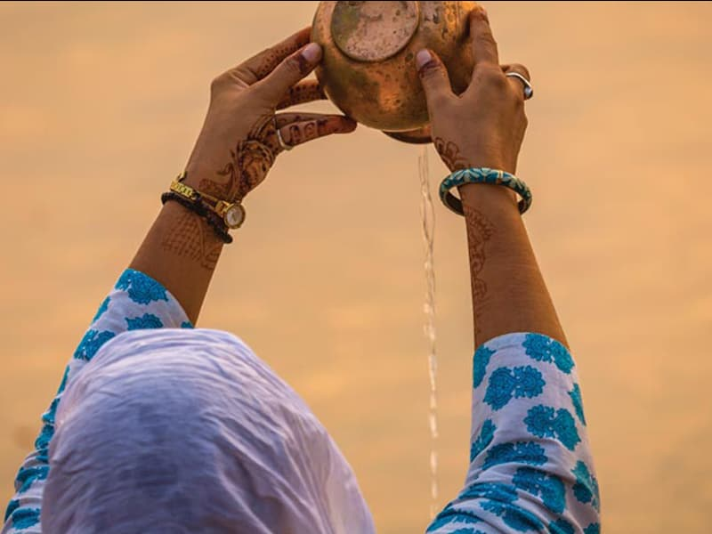 Woman pouring water, holding hands up high with henna on arm, hands, and fingers