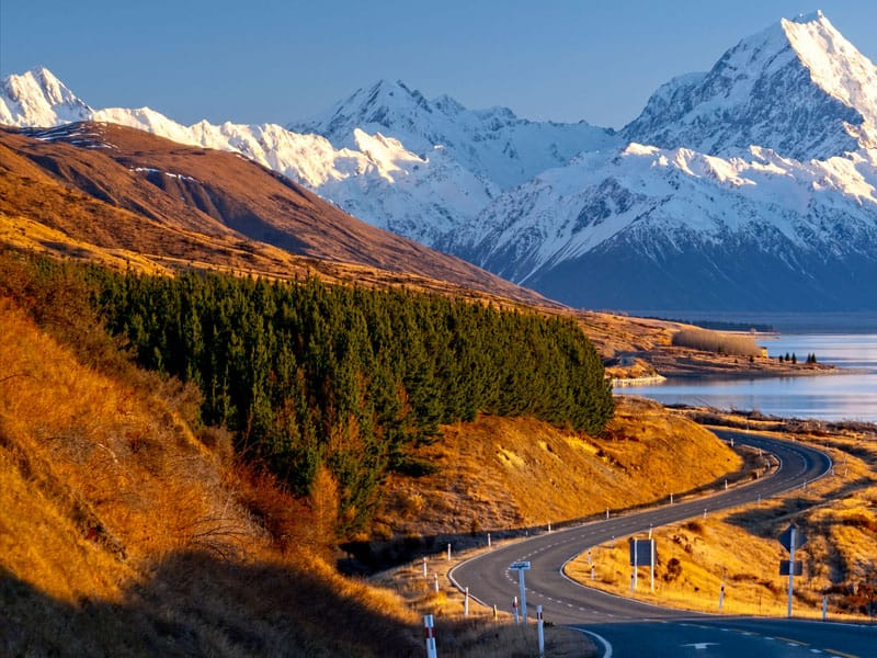 Scenic winding road along Lake Pukaki to Mount Cook National Park, South Island, New Zealand during cold and windy winter morning.