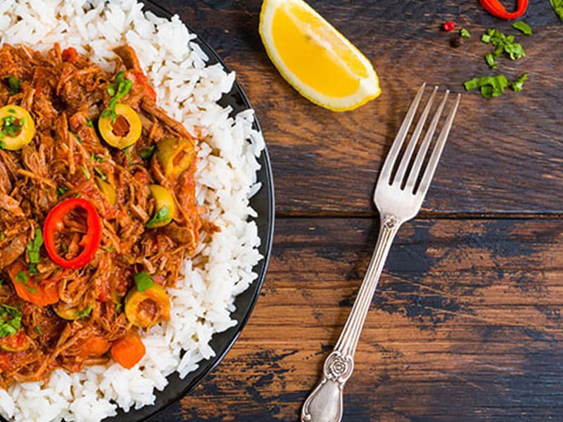 Regent Seven Seas plate of dinner food, shredded meat with olives and peppers on white rice, with fork and lemon