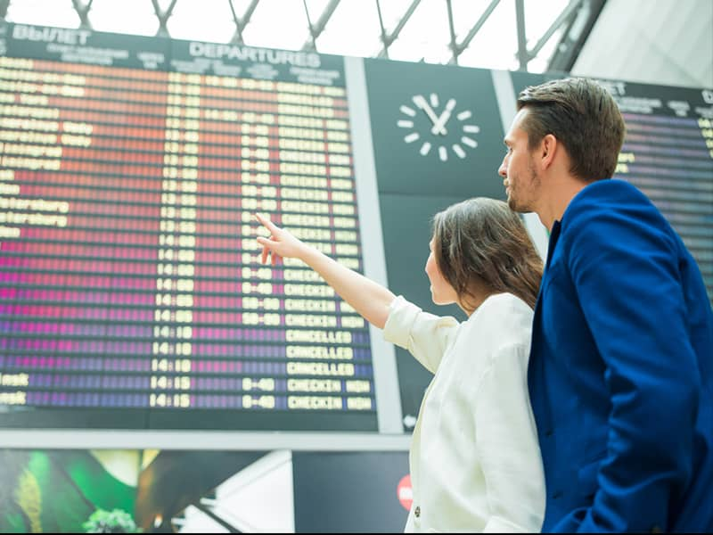 portrait of a young couple in front of a flight information board at an airport. The woman is pointing up at the board