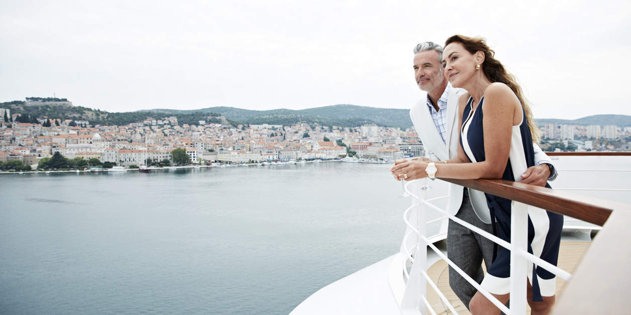 Man and woman overlooking city from Seabourn cruises obsevation deck